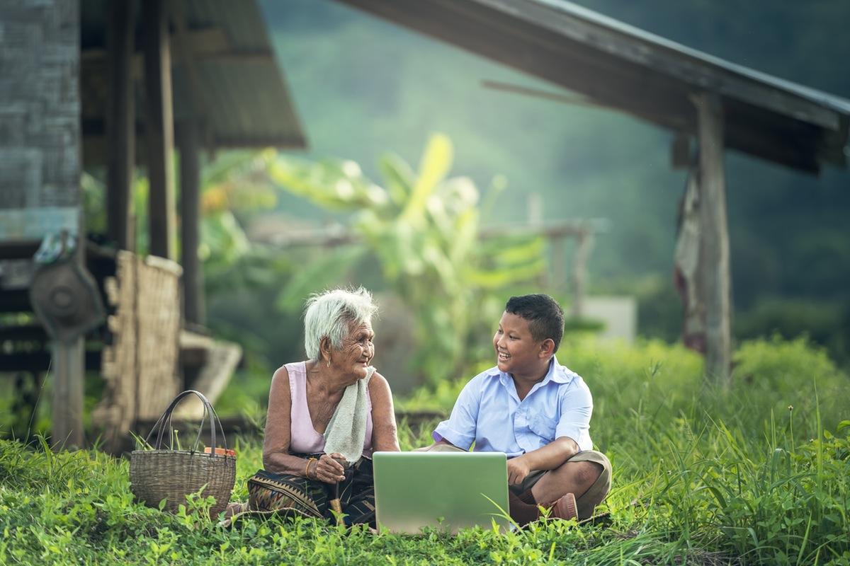 Un niño asiático con su abuela viendo un dispositivo portátil sentados en el pasto