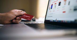 Tarjeta de crédito siendo usada en un laptop para comprar servicios en línea.